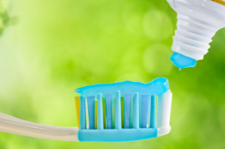 Dental brush and tube with paste on nature blurred background Stock Photo