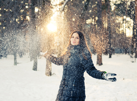 Happy young woman having fun in the snow photo