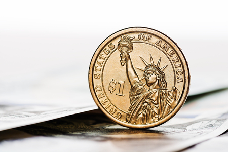 one us dollar coin on american banknotes