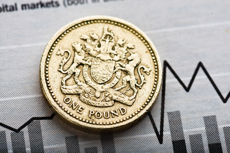 depreciation: One pound coin on fluctuating graph. Rate of the pound sterling (shallow DOF). Stock Photo