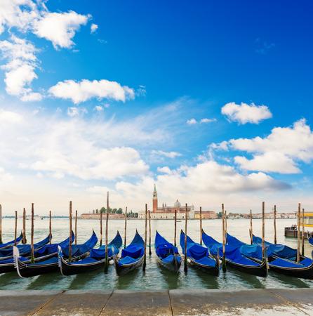 Gondolas moored by Saint Mark square with San Giorgio di Maggiore church in the background - Venice,  Italy, Europe Stock Photo