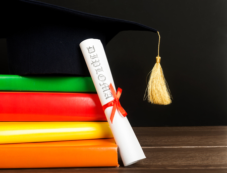 A mortarboard and graduation scroll, tied with red ribbon, on a stack of books  免版税图像