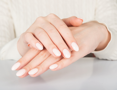 Beautiful female hand with beige nail design. Stock Photo
