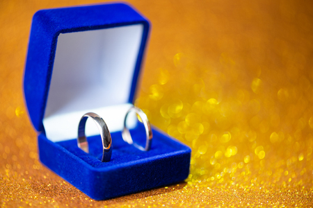 gold wedding rings in the blue jewelery box. Glitter background