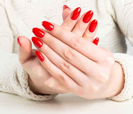 hands of a young woman with dark red manicure Stock Photo
