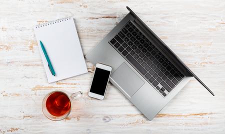 Schreibtisch mit Laptop, Planer, mobilem Smartphone und Tasse Tee Standard-Bild