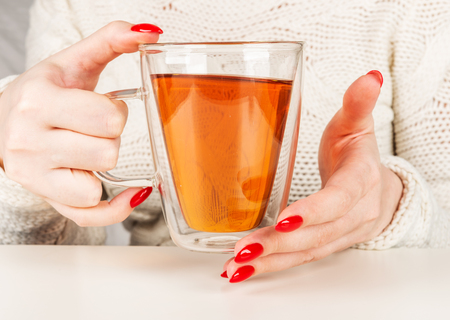 female hands holding a transparent cup of hot tea. Beautiful red manicure 스톡 콘텐츠