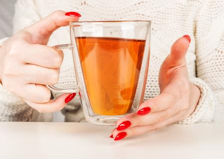 female hands holding a transparent cup of hot tea. Beautiful red manicure Foto de archivo
