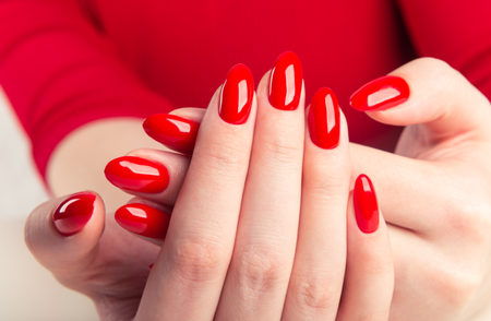 hands of a young woman with red manicure