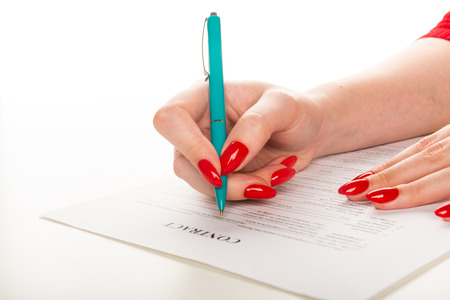 womans hand with pen signing document