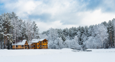 Wooden house in a nature area covered with freshly fallen snow Stock Photo