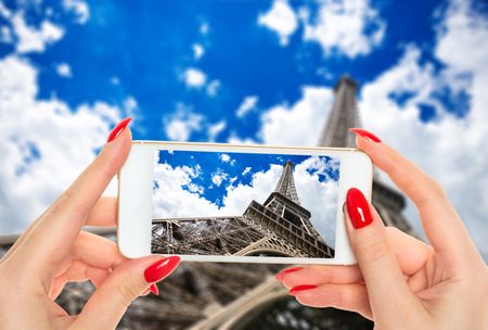 Woman taking a picture of famous Eiffel Tower in Paris, France.