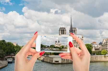 Woman taking a picture of Notre Dame de Paris Cathedral.Paris. France 写真素材