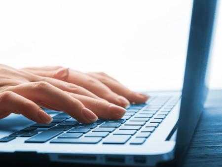 Primer plano de escribir manos femeninas en el teclado