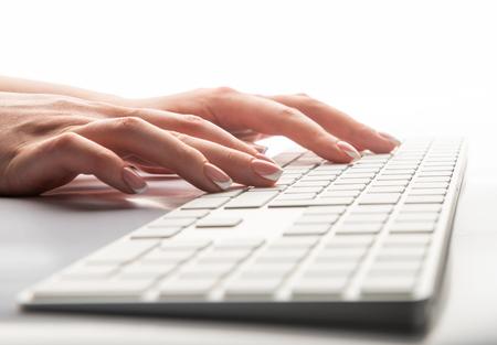 Primo piano di digitare mani femminili sulla tastiera