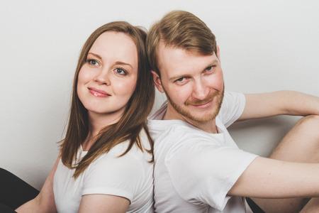 Hombre y mujer felices alegres sentados espalda con espalda.