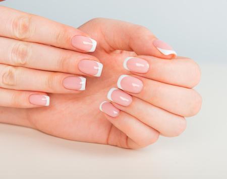 Manos de mujer hermosa con uñas hermosas después del salón de manicura con manicura francesa