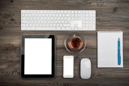 mesa de oficina con teclado de computadora, mouse, taza de té, tableta y teléfono inteligente Foto de archivo