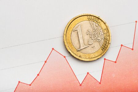 One euro coin on fluctuating graph. Rate of euro (shallow DOF)