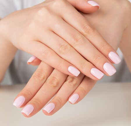 Beautiful female hand with light pink nail design. Imagens