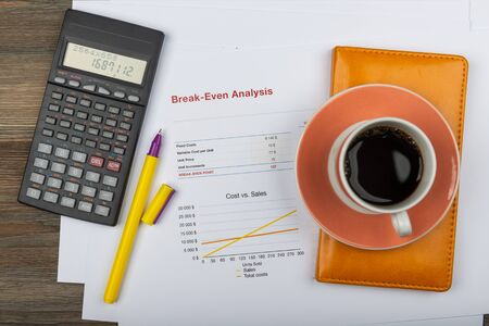 Office workplace table with report pages, coffee cup and calculator Фото со стока