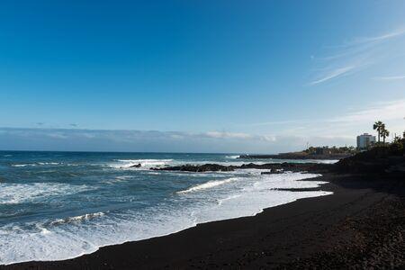 Tropical unusual exotic beach with black volcanic sand. Playa Jardin,Puerto de la Cruz, Tenerife, Spain Фото со стока