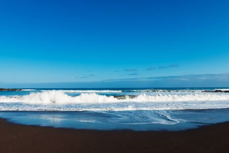 beach with black volcanic sand and ocean