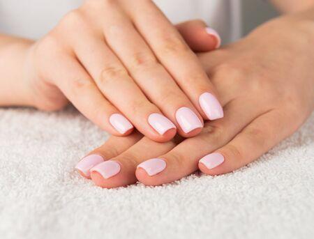 Beautiful female hand with light pink nail design. Фото со стока