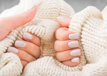 Stylish pastel beige Nails holding knitted wool material Фото со стока - 134116396