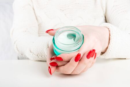 Beautiful hands of young woman with the jar of cream