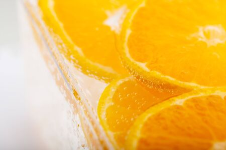 Fresh orange slice in water with bubbles