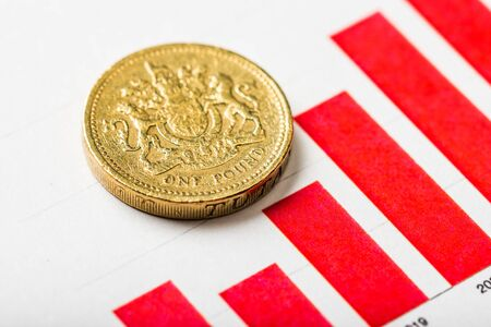 One pound coin on fluctuating graph. Rate of the pound sterling (shallow DOF) Фото со стока - 134116454