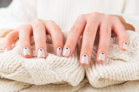 Stylish beige Nails with dots holding knitted wool material Фото со стока - 134116455