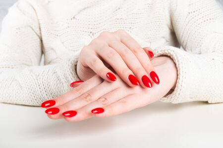 hands of a young woman with red manicure Фото со стока - 134116517