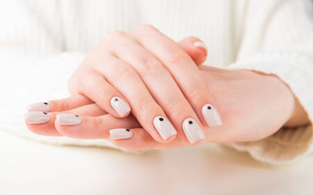 female hand with beige manicure with dots nail design.
