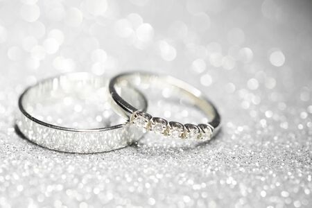 pair of platinum wedding rings. Glitter background Фото со стока