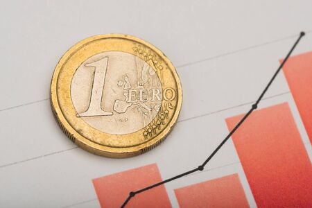 One euro coin on fluctuating graph. Rate of euro (shallow DOF) Фото со стока