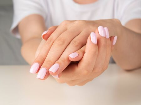Beautiful female hand with light pink nail design. Фото со стока