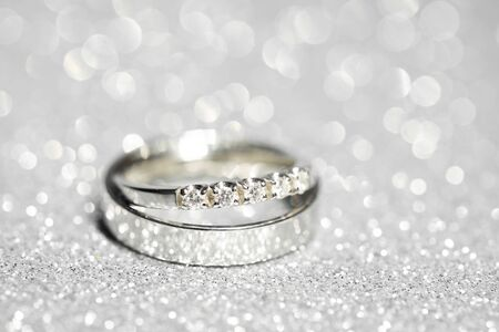 pair of platinum wedding rings. Glitter background