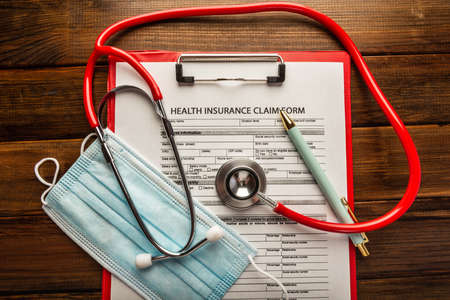 Health insurance claim form with stethoscope and surgical mask