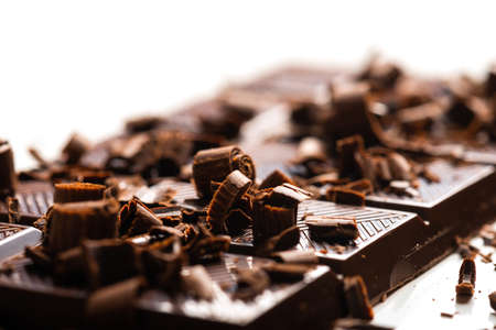 Curls and pieces of tasty chocolate on white table Фото со стока