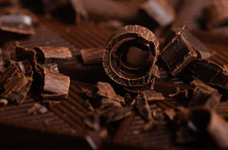 Composition of pieces of dark chocolate and curls and pieces
