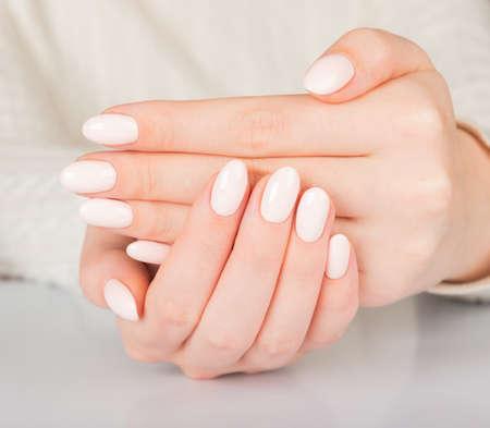 Beautiful female hand with beige nail design. Фото со стока