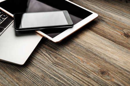 laptop with phone and tablet pc on wooden desk