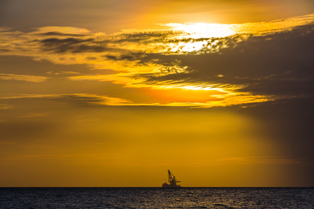 sun energy: Floating oil platform on sea sunset. Hainan, China. The sun gives the last rays to the orange sky.