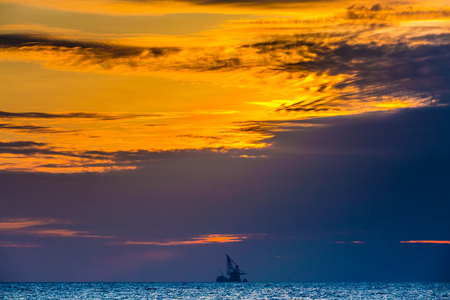 Floating oil platform on sea sunset. Hainan, China. The sun gives the last rays to the orange sky.