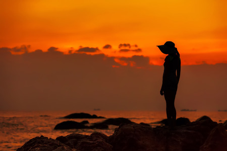 Silhouette of a girl in a hat against the background of an orange sea sunset. End of the Earth. Hainan, China.