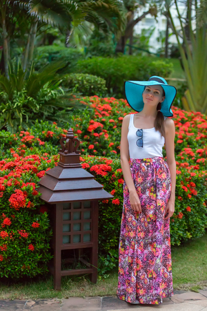 A girl in azure hat with fields, a white tshirt and a long pink skirt, against the background of a Chinese lantern and a flower bed. Sanya, Hainan Island, China.