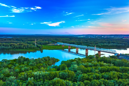 A railway bridge across a calm river surrounded by green magical forest at sunset with a beautiful blue sky, copy space for text. White river, green UFA, Welcome to Russia.