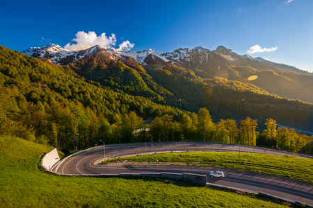 A road serpentine on a background of green forest slopes and snowy mountain top. Road to Mountain Olympic Village, Sochi.